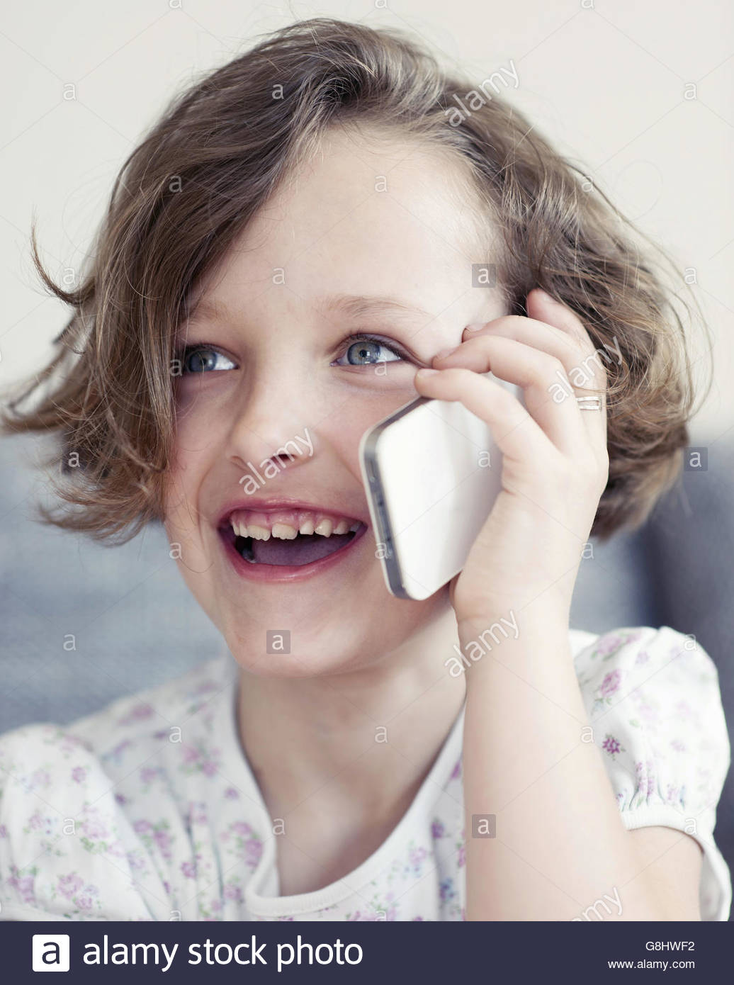 Young girl using cellphone, smiling - Stock Image