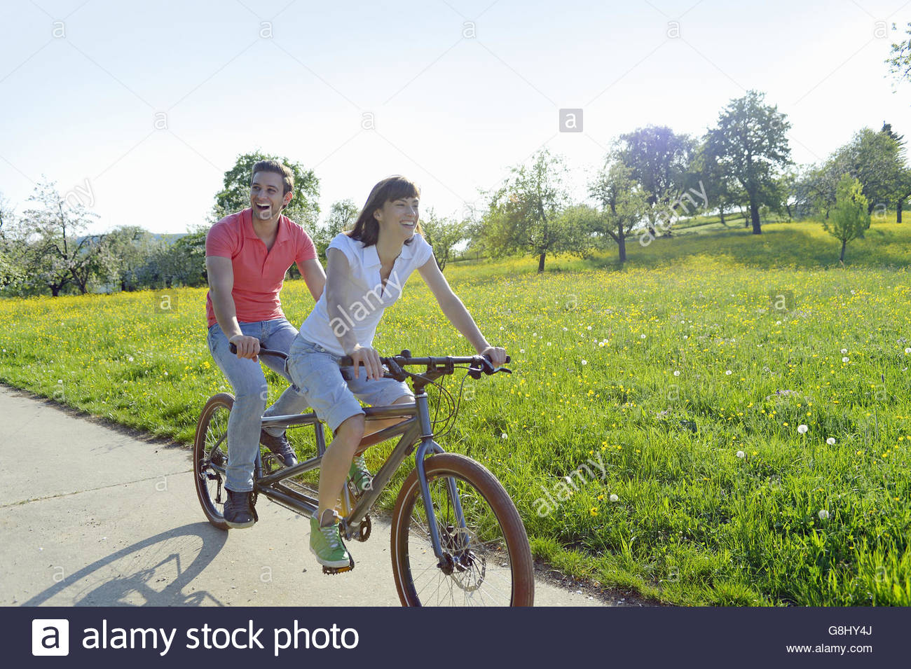 Young couple riding tandem through park - Stock Image