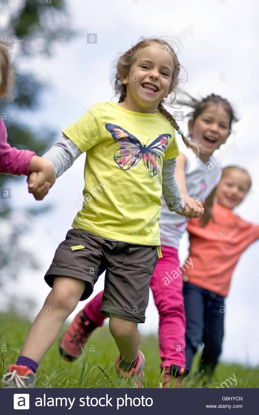 Kindergarten kids running in a wood kindergarten - Stock Image