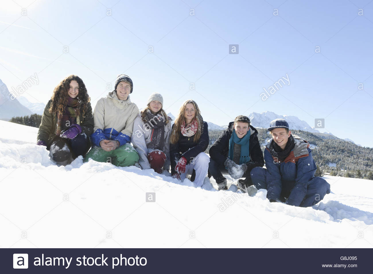 Portrait of young friends crouching on snow - Stock Image