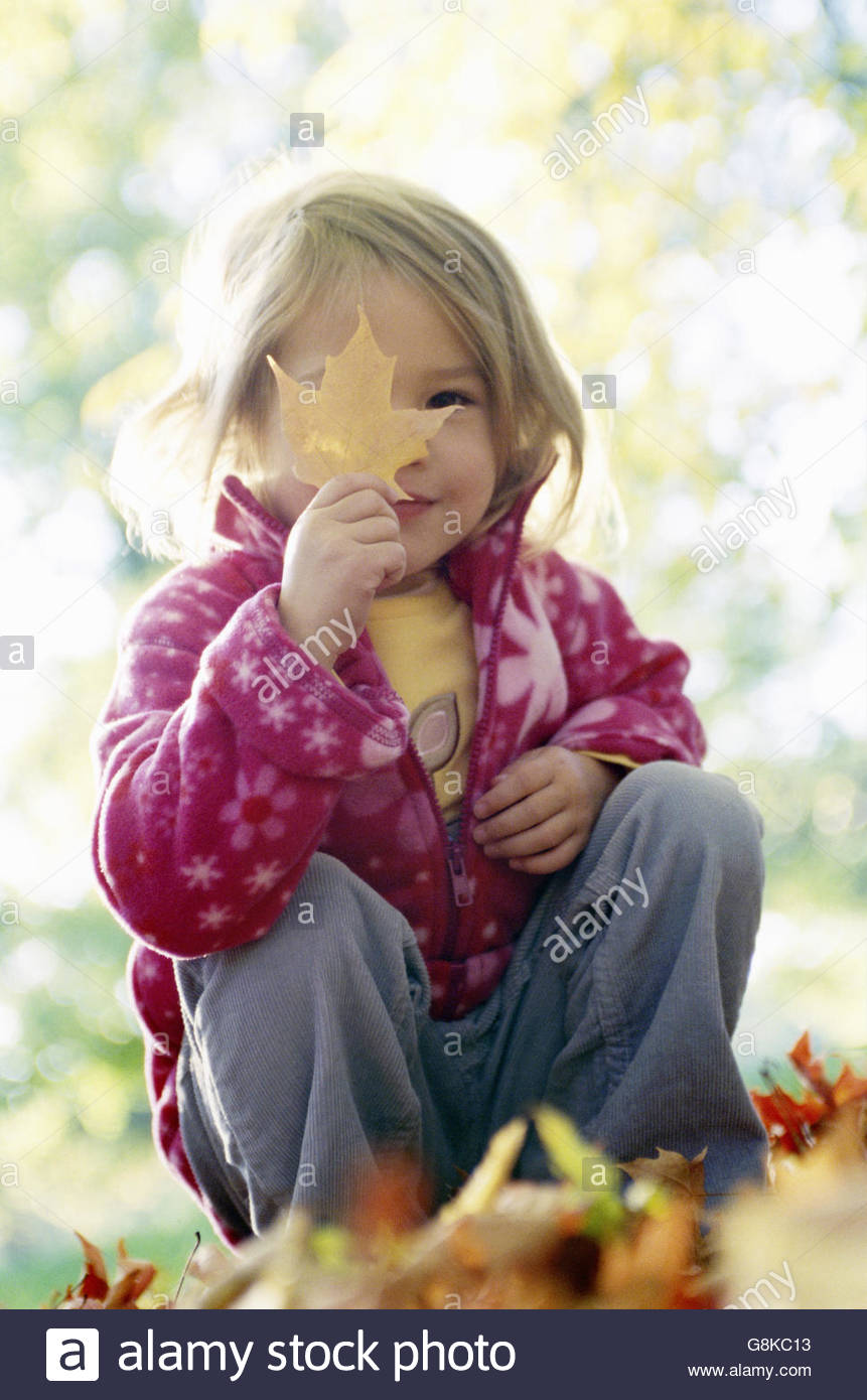 Young girl holding autumn leaf up in front of her face - Stock Image