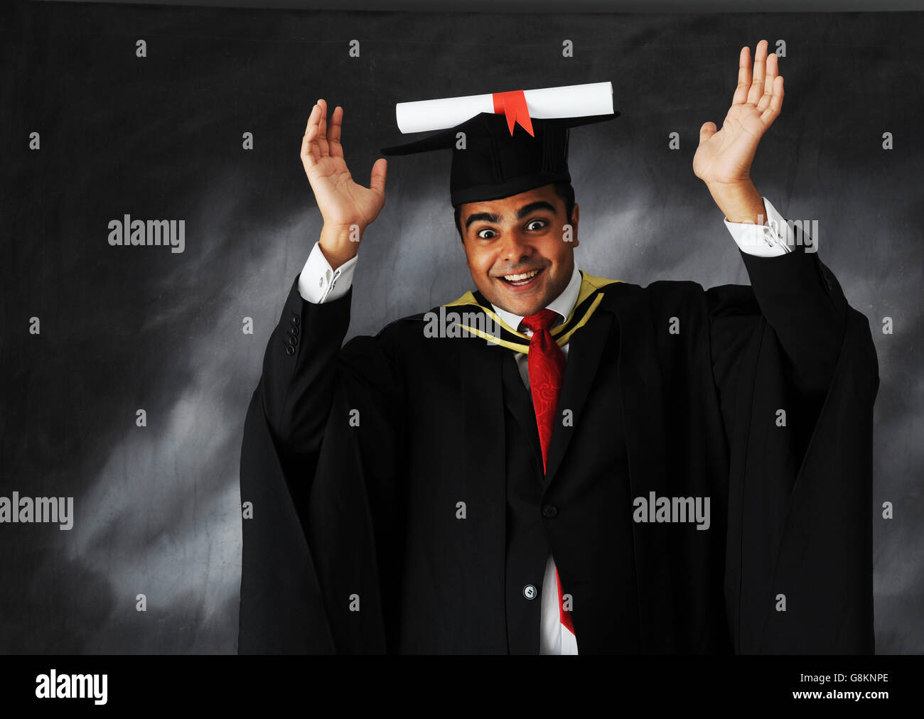 Studio shot of a male student graduate in gown with scroll on hat expressing enormous joy for achieving his university - Stock Image