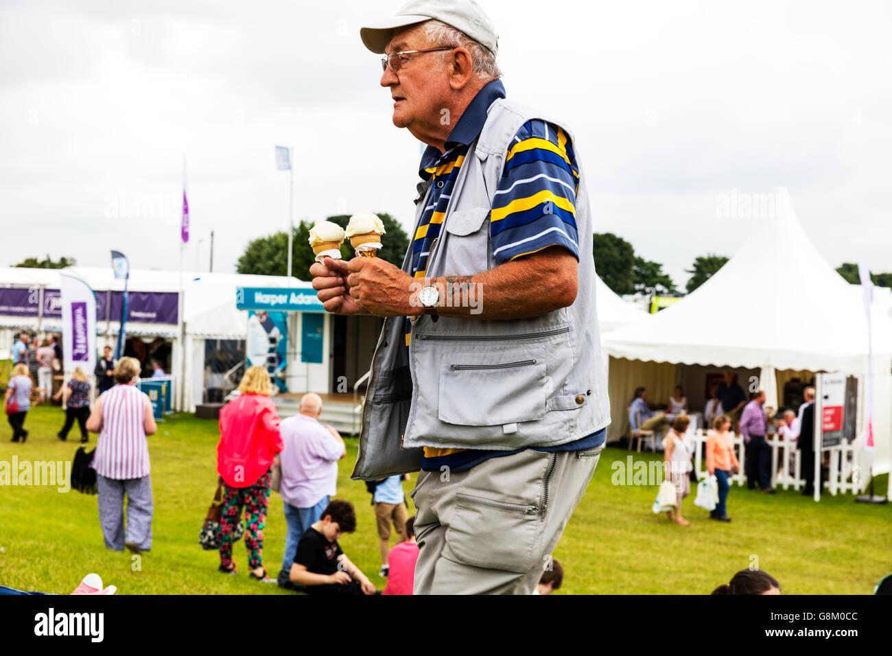 Man walking with ice creams icecreams cornets to family UK England GB - Stock Image