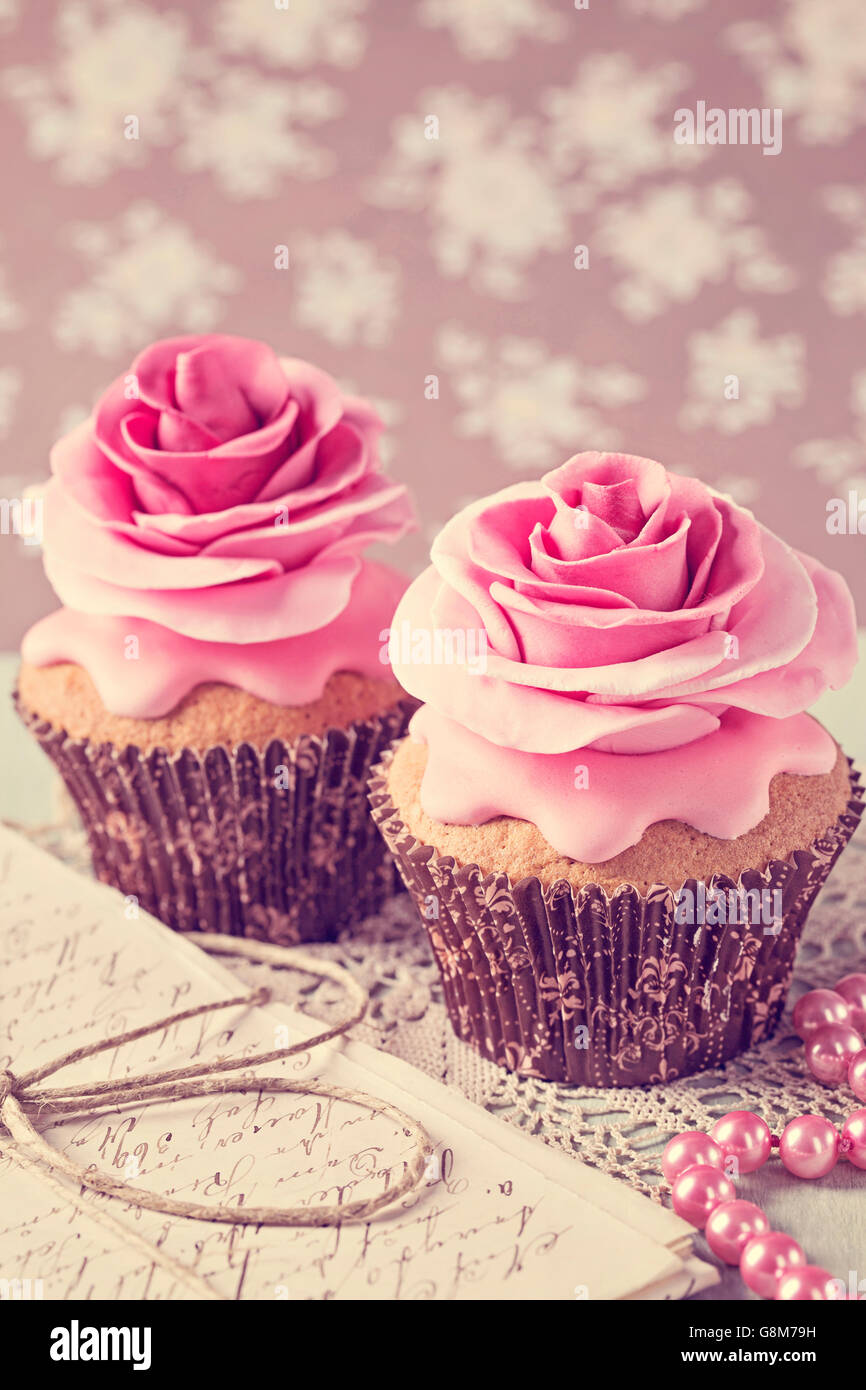 Two cupcakes with rose flowers and a letter - Stock Image