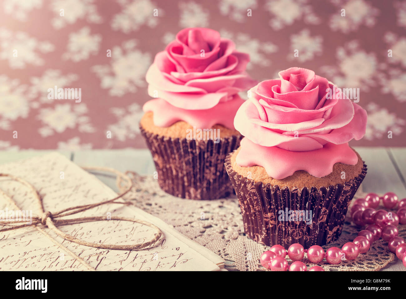Cupcakes with sweet rose flowers and a letter - Stock Image