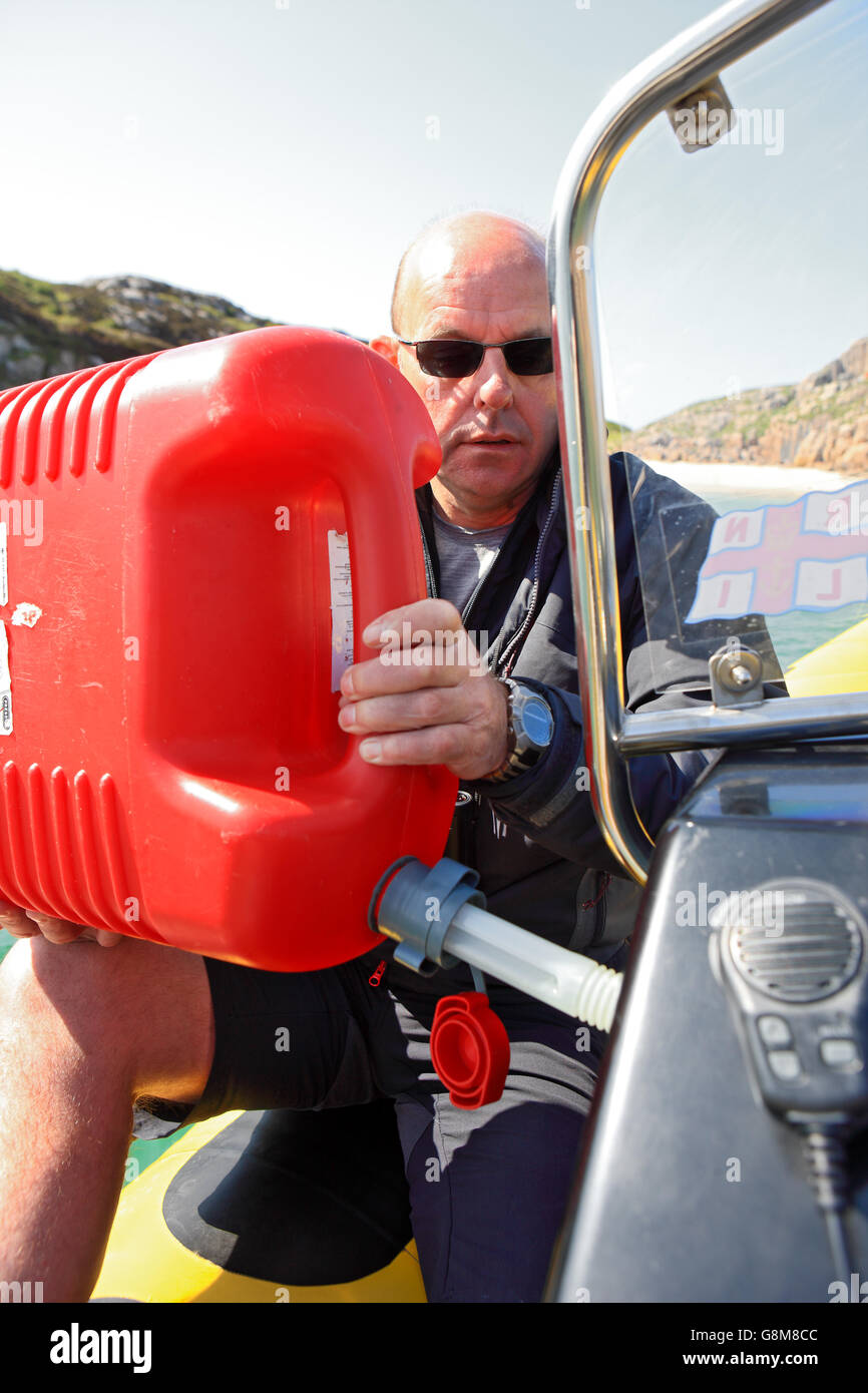 Man using a red plastic Jerry Can to fill up a RIB with petrol. - Stock Image