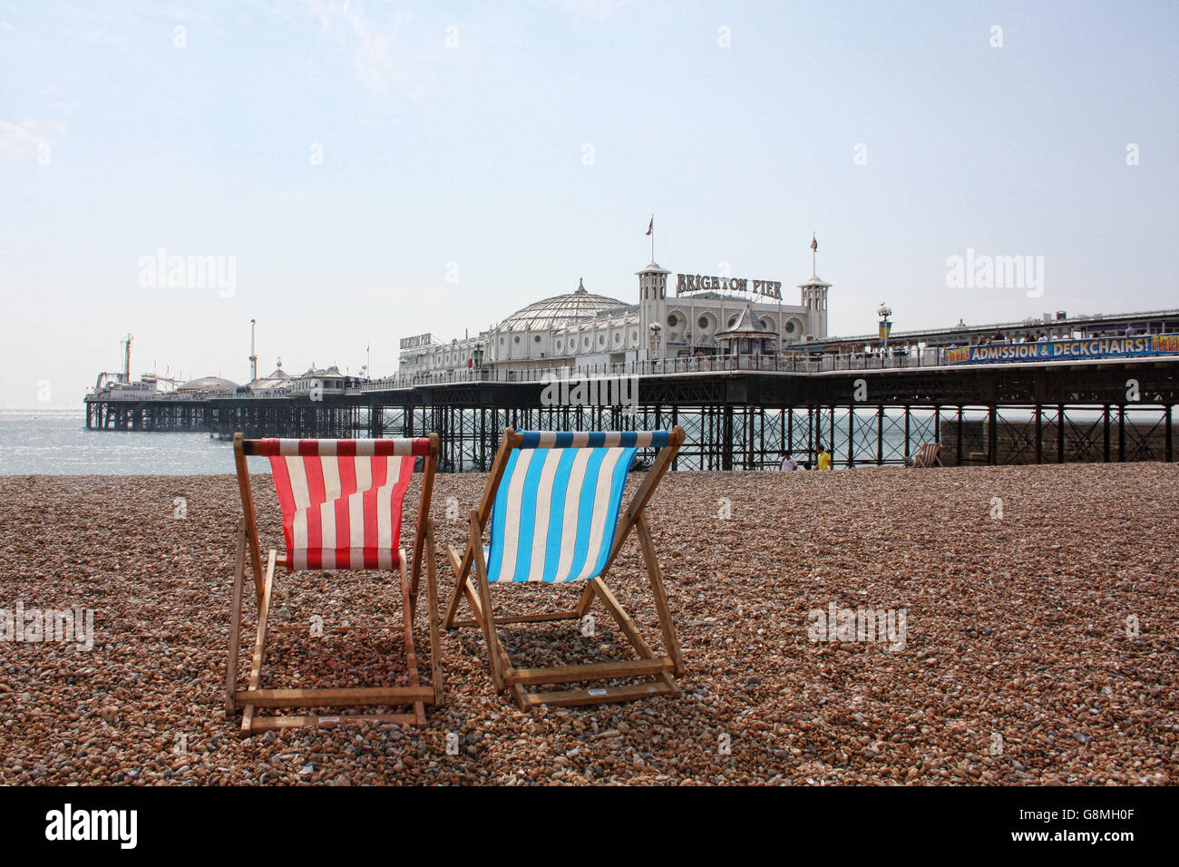 Deckchairs looking out at Brighton Pier - Stock Image