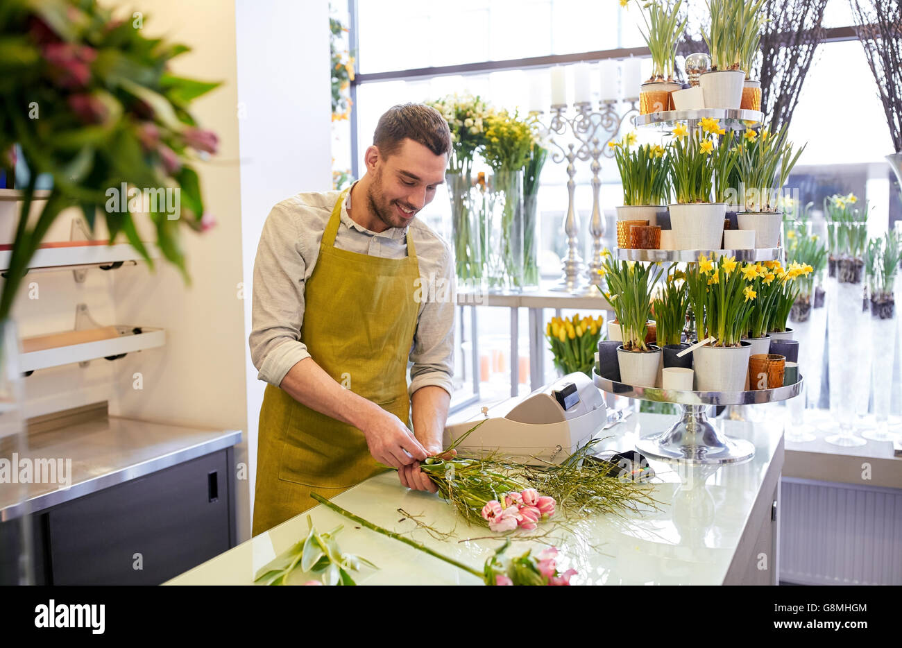 smiling florist man making bunch at flower shop - Stock Image
