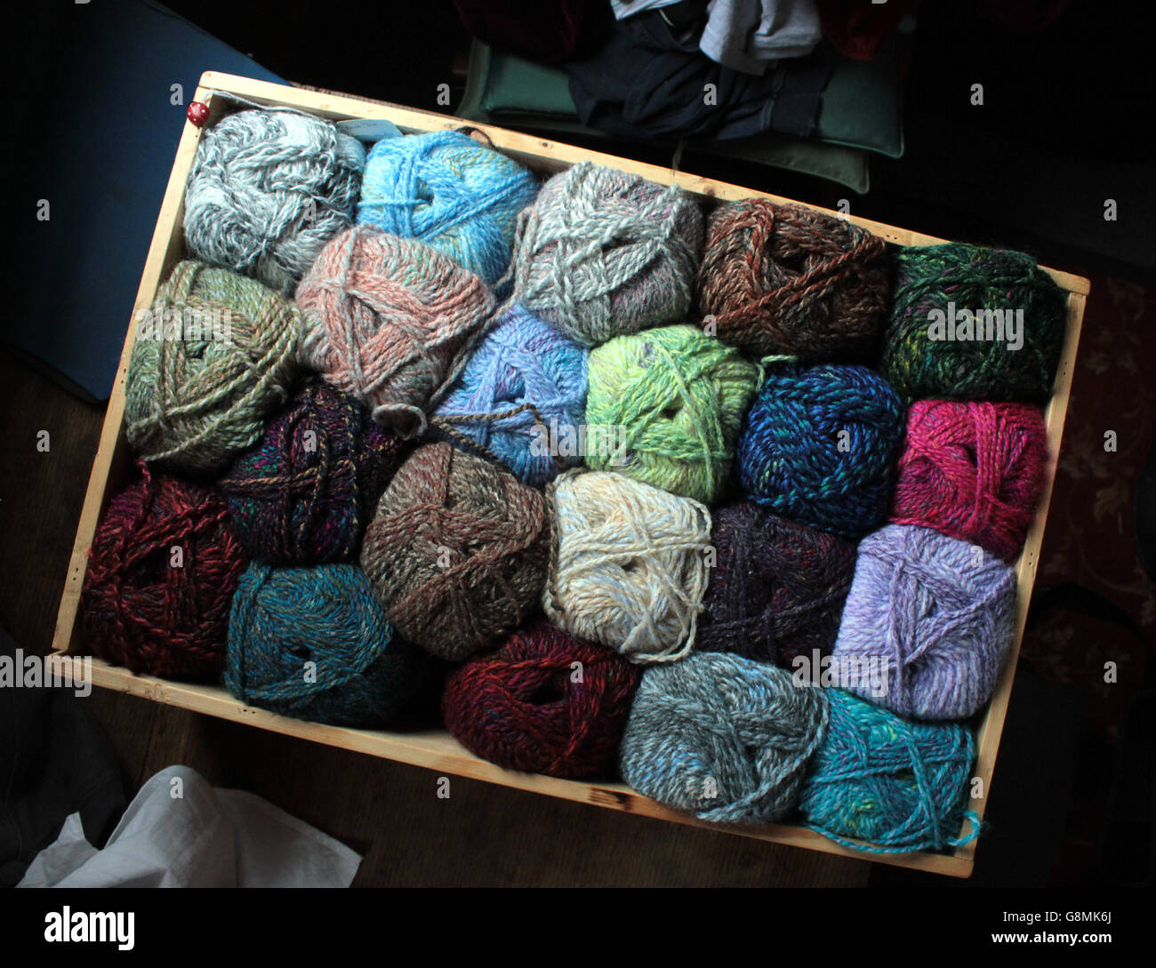 A display box of hand knitting yarns in various shades from blues, browns through to reds and greens. - Stock Image