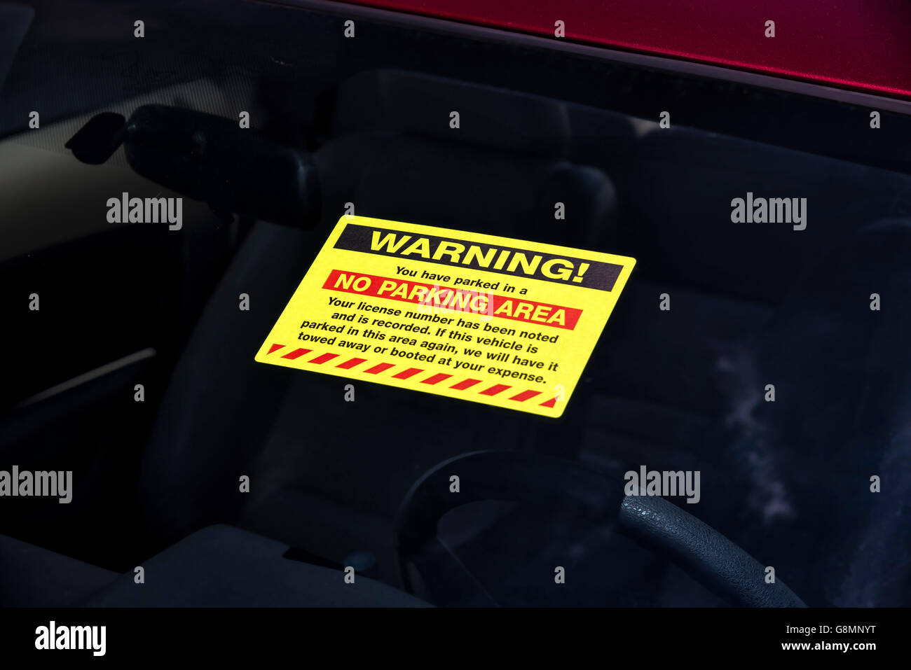 Parking violation sticker on windshield reading WARNING! for illegal parking. - Stock Image