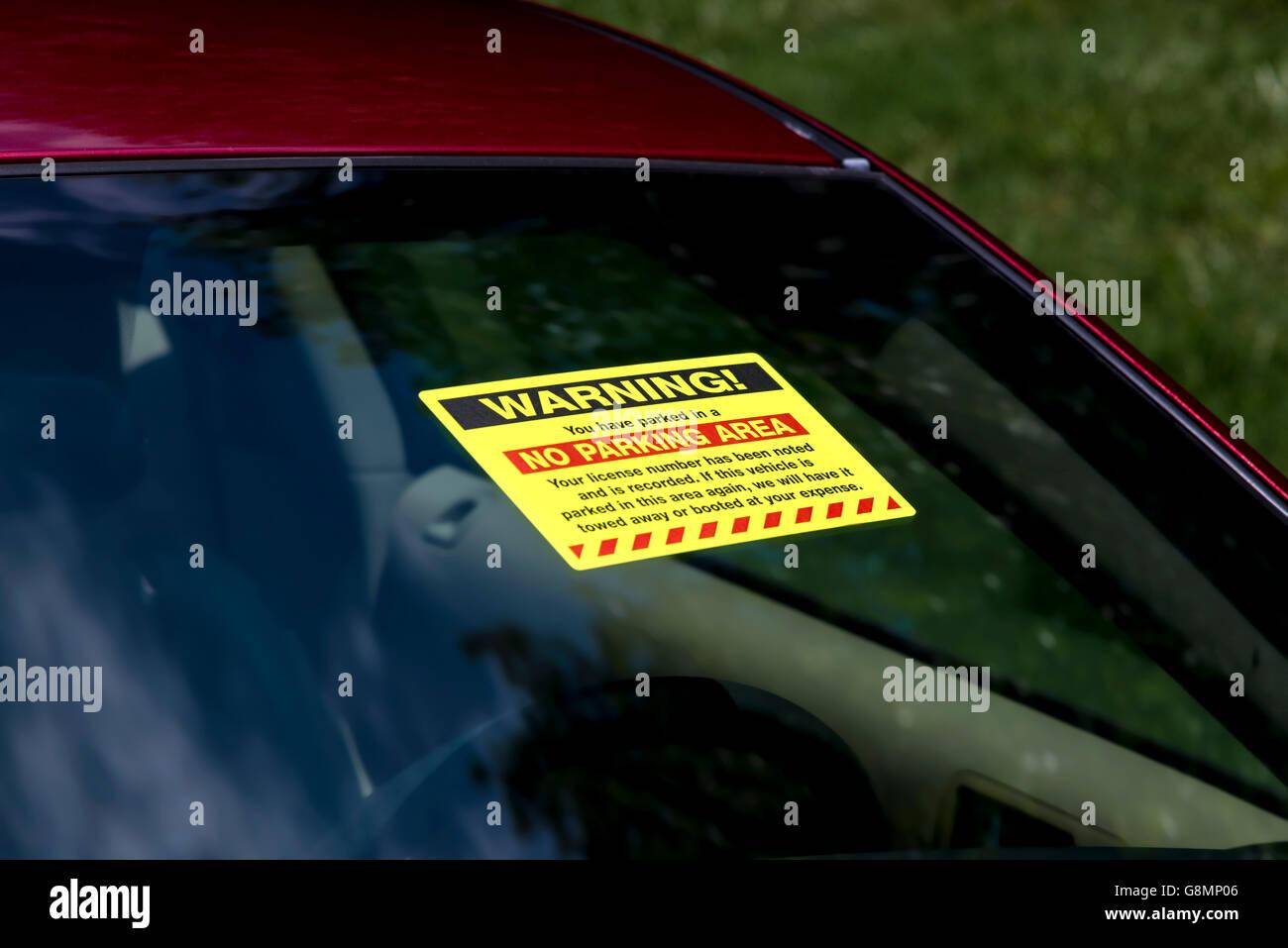 WARNING! Sticker on windshield of vehicle parked illegally. Horizontal shot - Stock Image