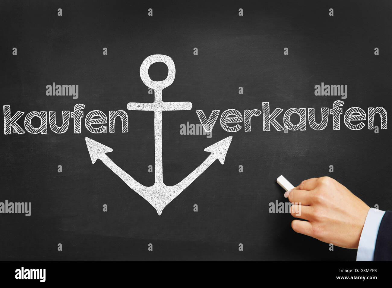 Hand writing the German words 'kaufen' (buy) and 'verkaufen' (sell) on blackboard - Stock Image