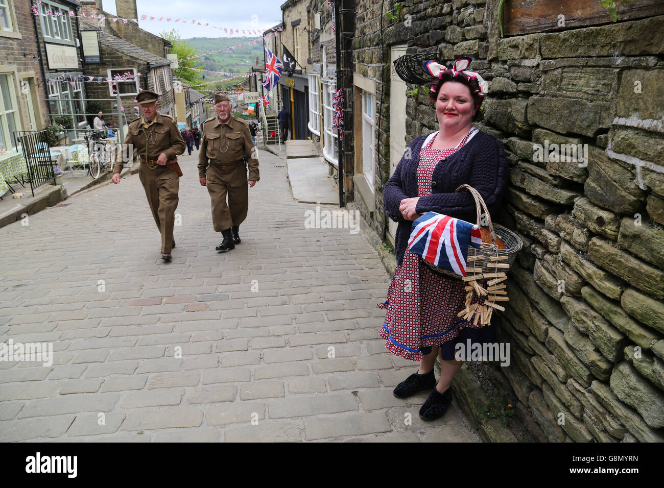 A woman dressed in costume smiles as two men dressed in home guard uniforms walk past during the annual 1940's event - Stock Photo