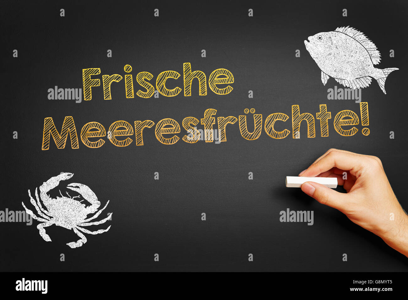 Hand with chalk writing in German 'Frische Meeresfruechte!' (Fresh Sea Food) on a blackboard - Stock Image