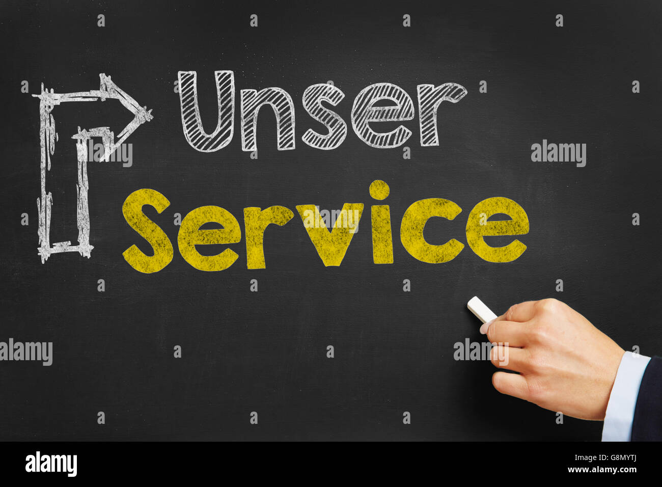 """Hand writes in German """"Unser Service"""" (our service) with arrow on blackboard Stock Photo"""
