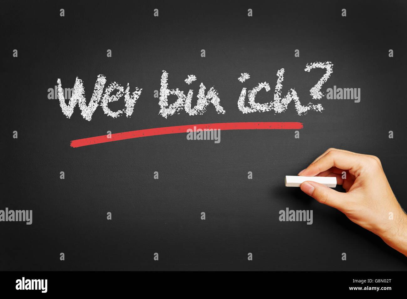 Hand writes in German 'Wer bin ich?' (Who am I?) on blackboard - Stock Image