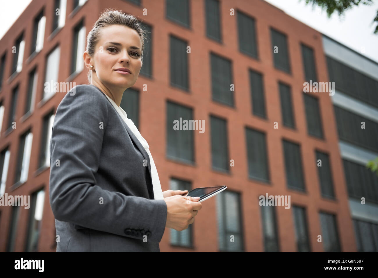 The new business. Portrait of modern business woman with tablet PC against office building - Stock Image