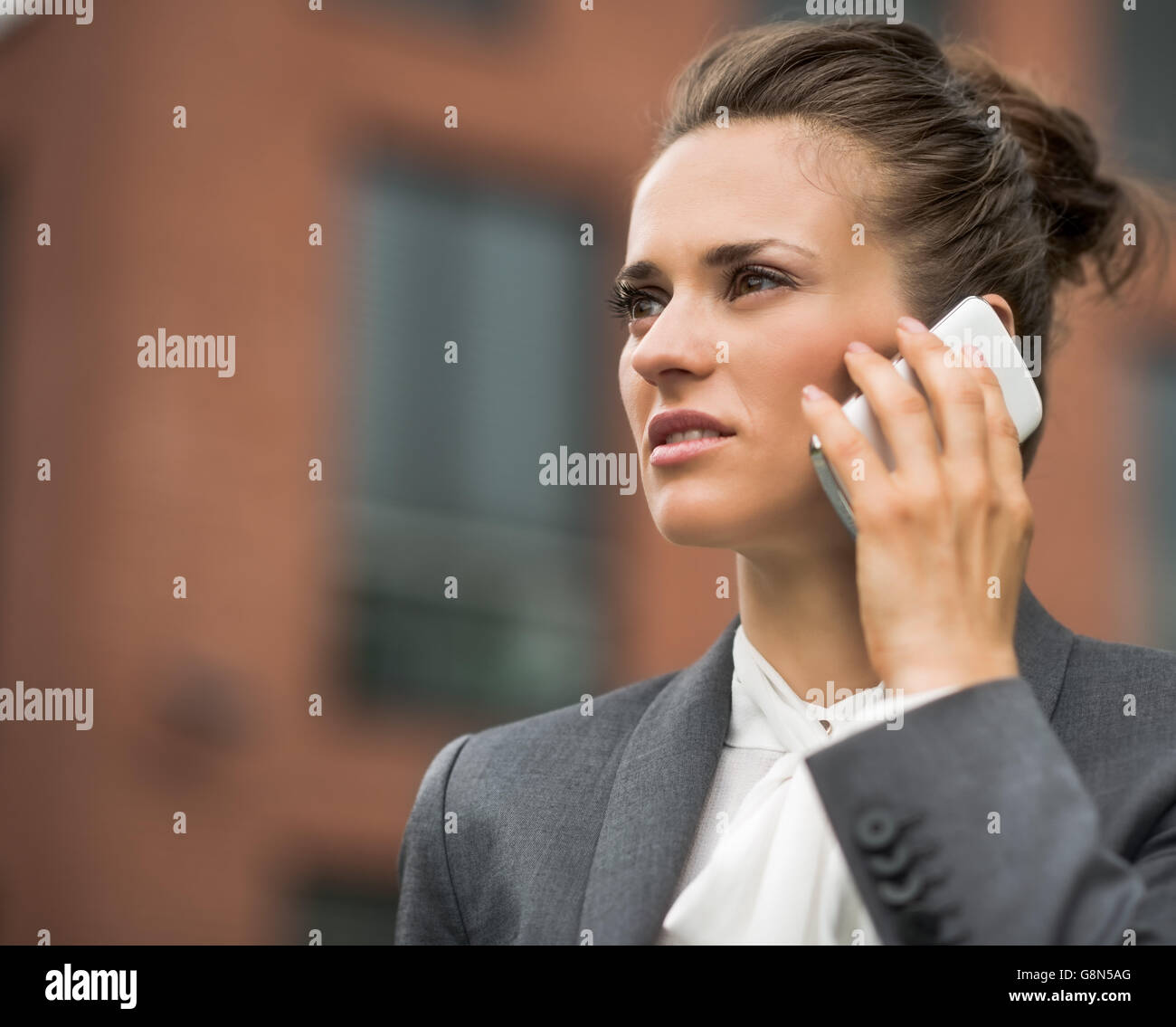 The new business. Modern business woman against office building talking smartphone - Stock Image