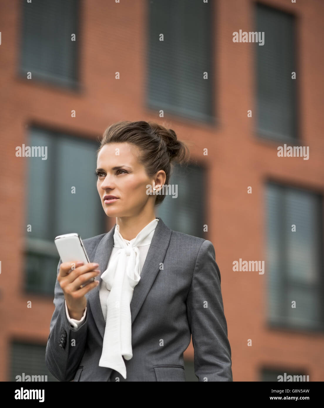 The new business. Modern business woman against office building with smartphone - Stock Image