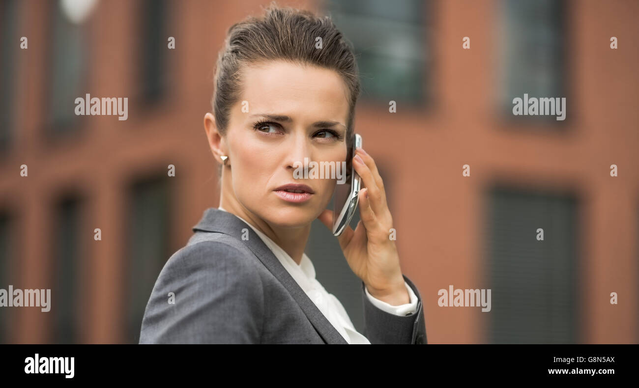 The new business. Portrait of serious modern business woman against office building talking smartphone - Stock Image