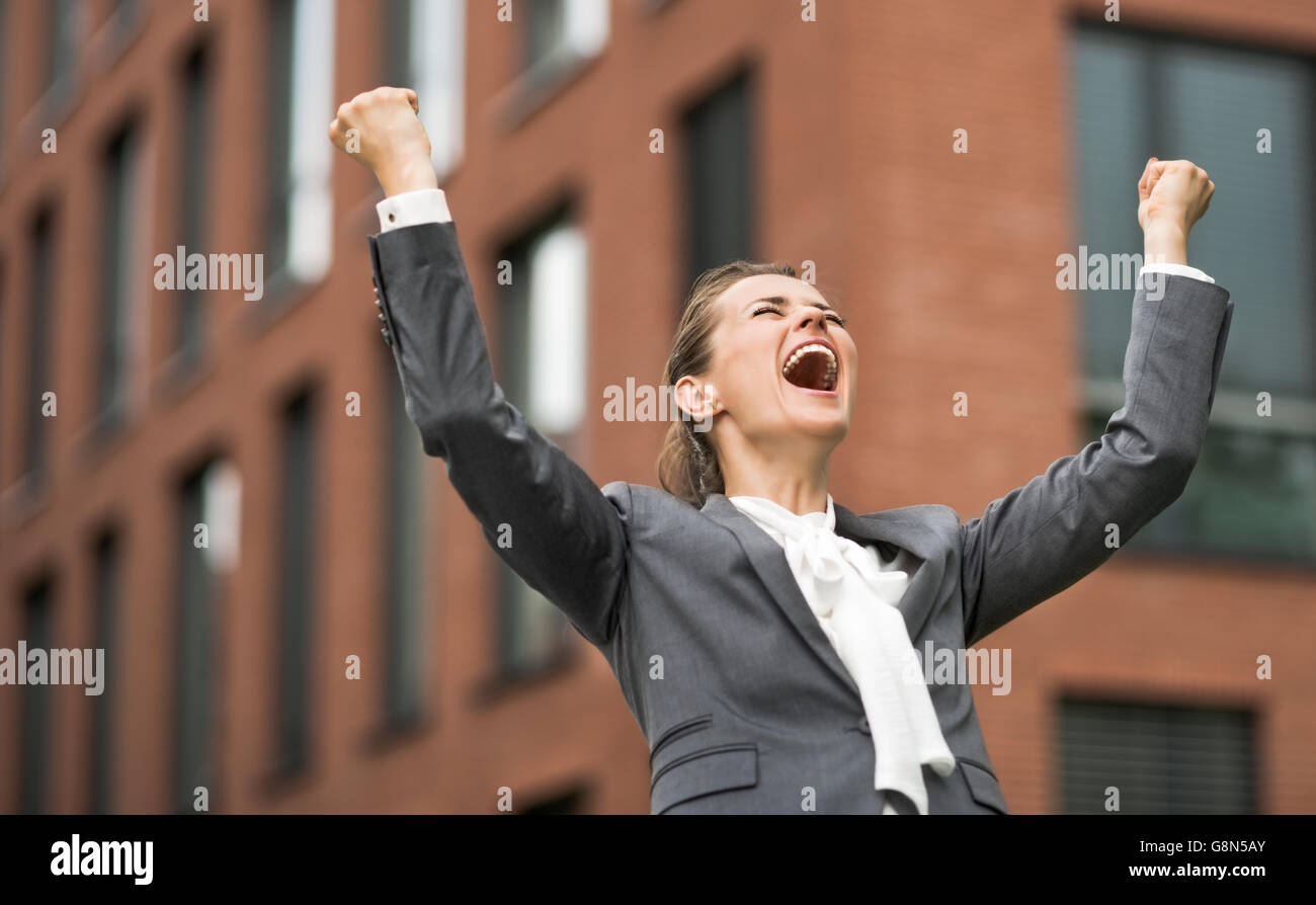 The new business. Happy modern business woman against office building rejoicing - Stock Image