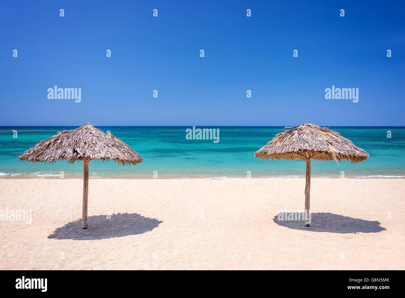Straw umbrella on a beautiful tropical beach - Stock Image