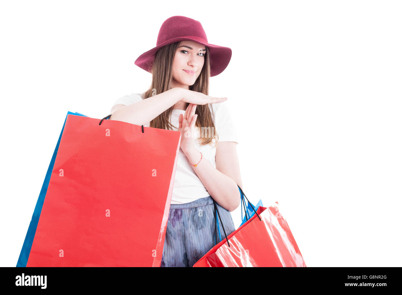 Smiling beautiful woman doing a pause or time out gesture at shopping isolated on white with advertising area - Stock Image