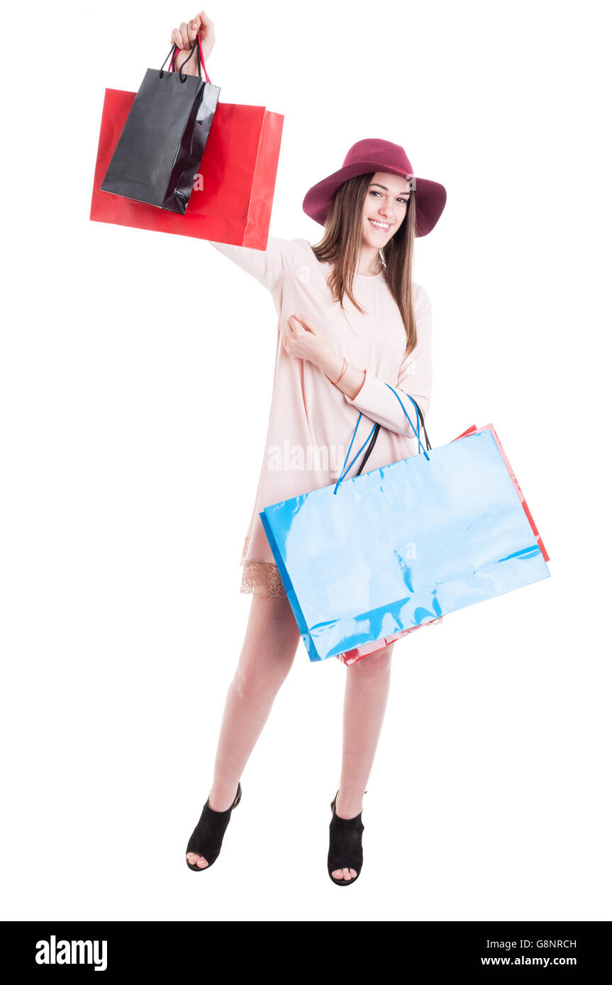 Cheerful beautiful girl in trendy outfit rising up shopping bags with copyspace isolated on white background - Stock Image