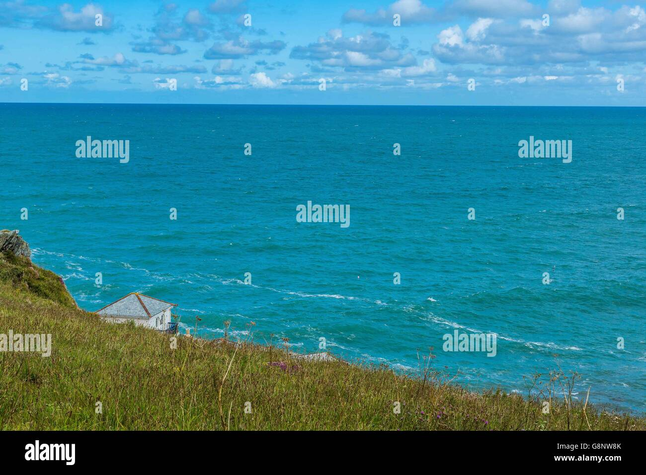 The Lewinnick Lodge at West Pentire waves and the blue sea ocean off the Cornish coast UK - Stock Image