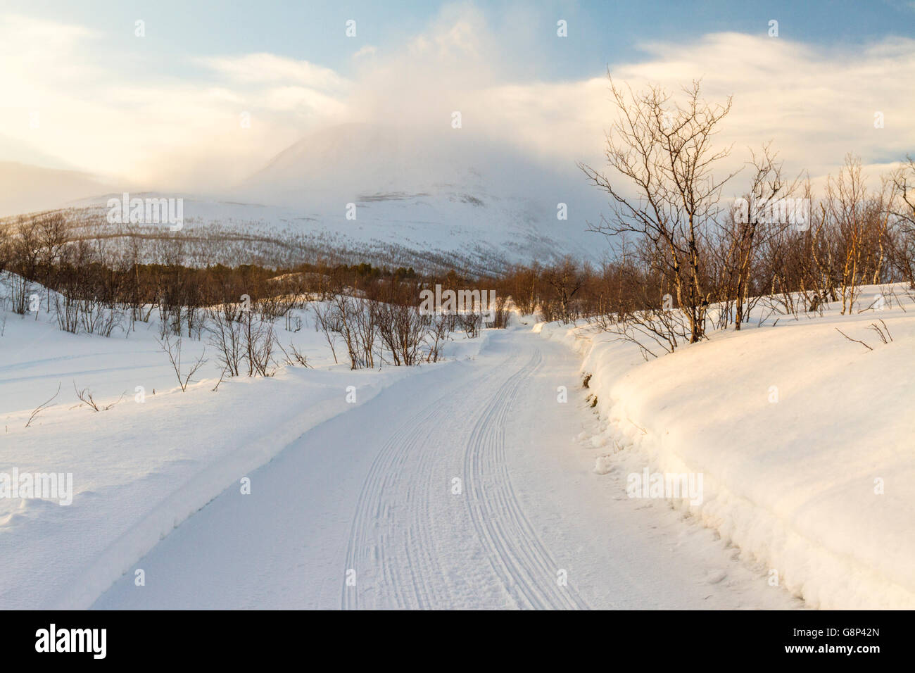 Winter landscape in Nikkaluokta with a winter road going towards big mountains in the background taken at sunset, Stock Photo