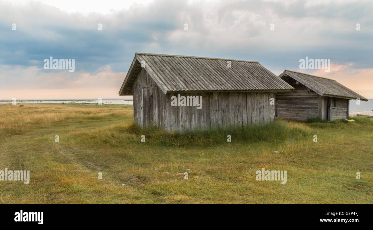 Two old barns in sunset at the sea shore at Petes on Gotland, Sweden - Stock Image