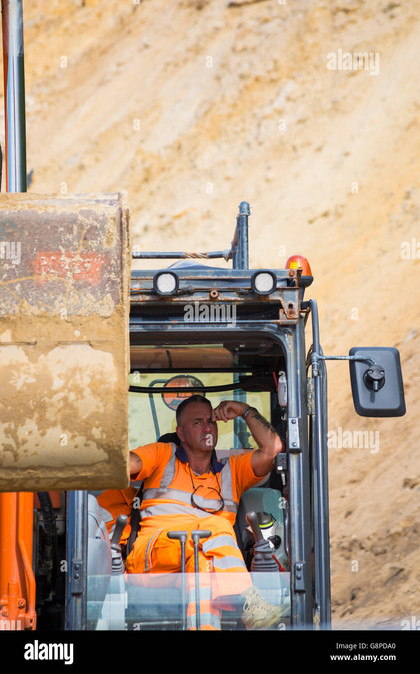 Workman in excavator machine in June for clearing debris from the landslide that occurred in April at Bournemouth - Stock Image