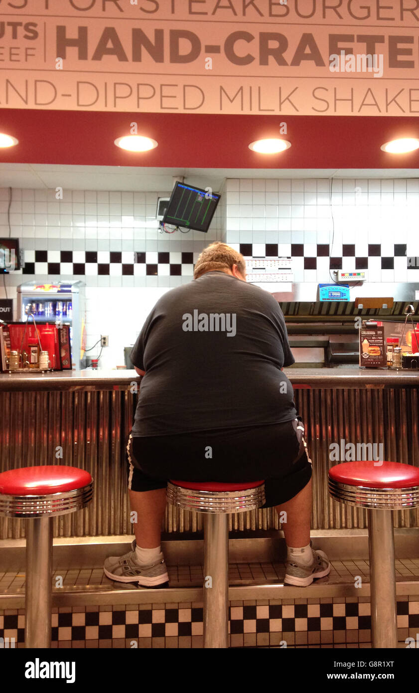 Fat obese man graphic image at a fast food diner on stool at counter - Stock Image