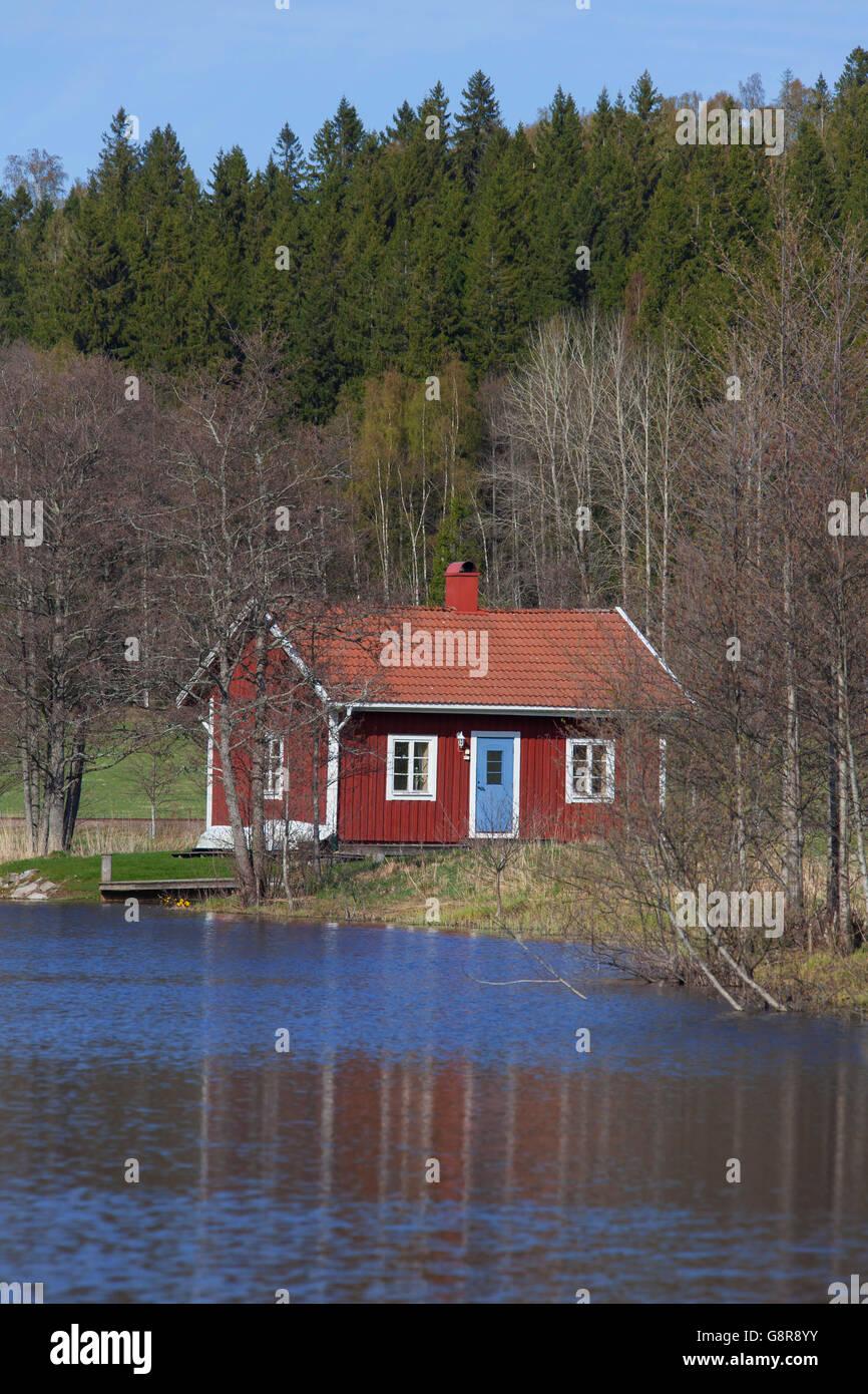 Swedish red wooden cabin along river in spring, Värmland, Sweden - Stock Image