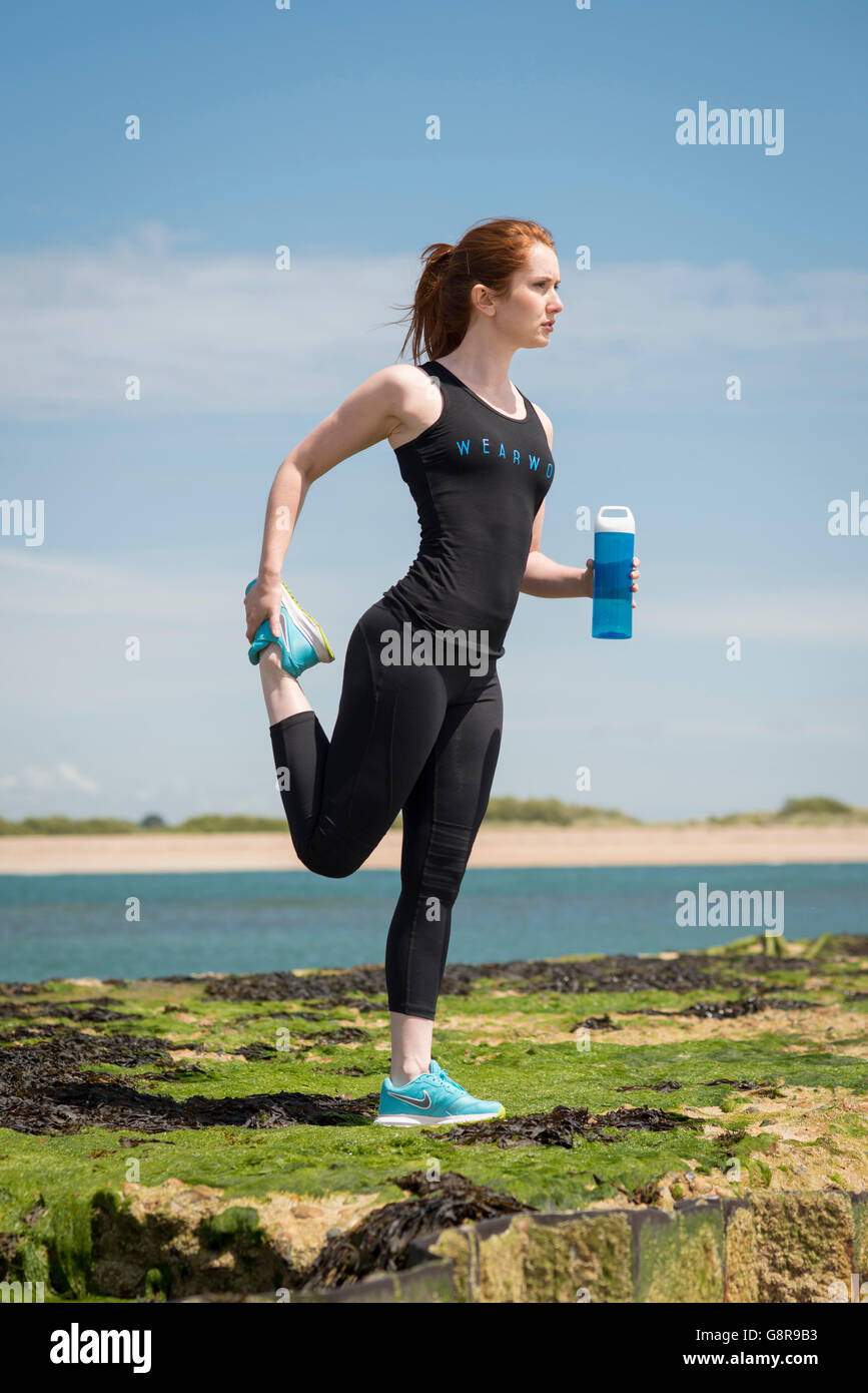 woman wearing sportswear drinking from a water bottle - Stock Image