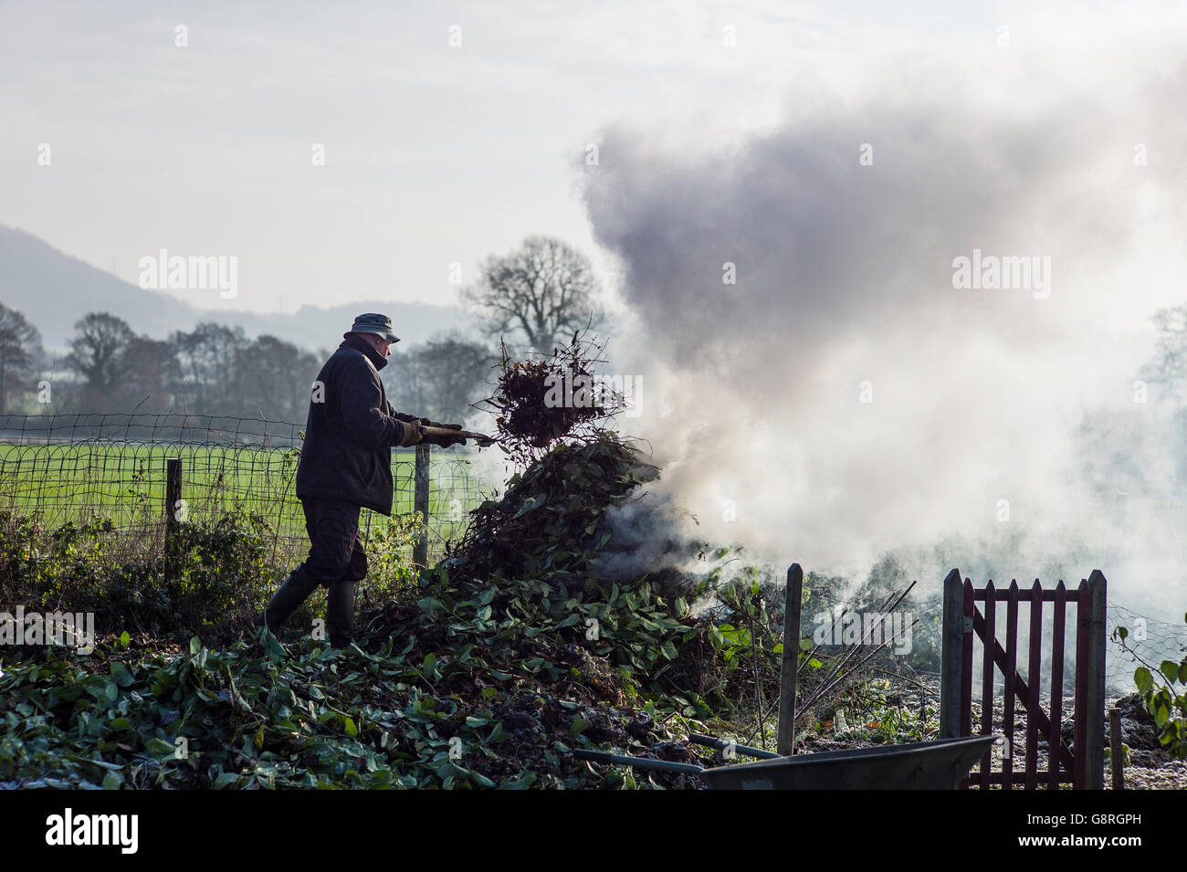 Burning garden waste in a country garden in winter - Stock Image