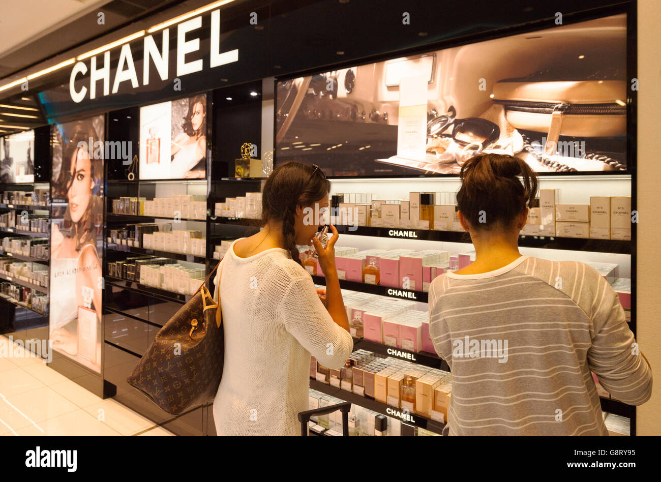 Two women shopping for Chanel perfume, Duty Free shop, Palma Airport, Majorca Spain Europe - Stock Image