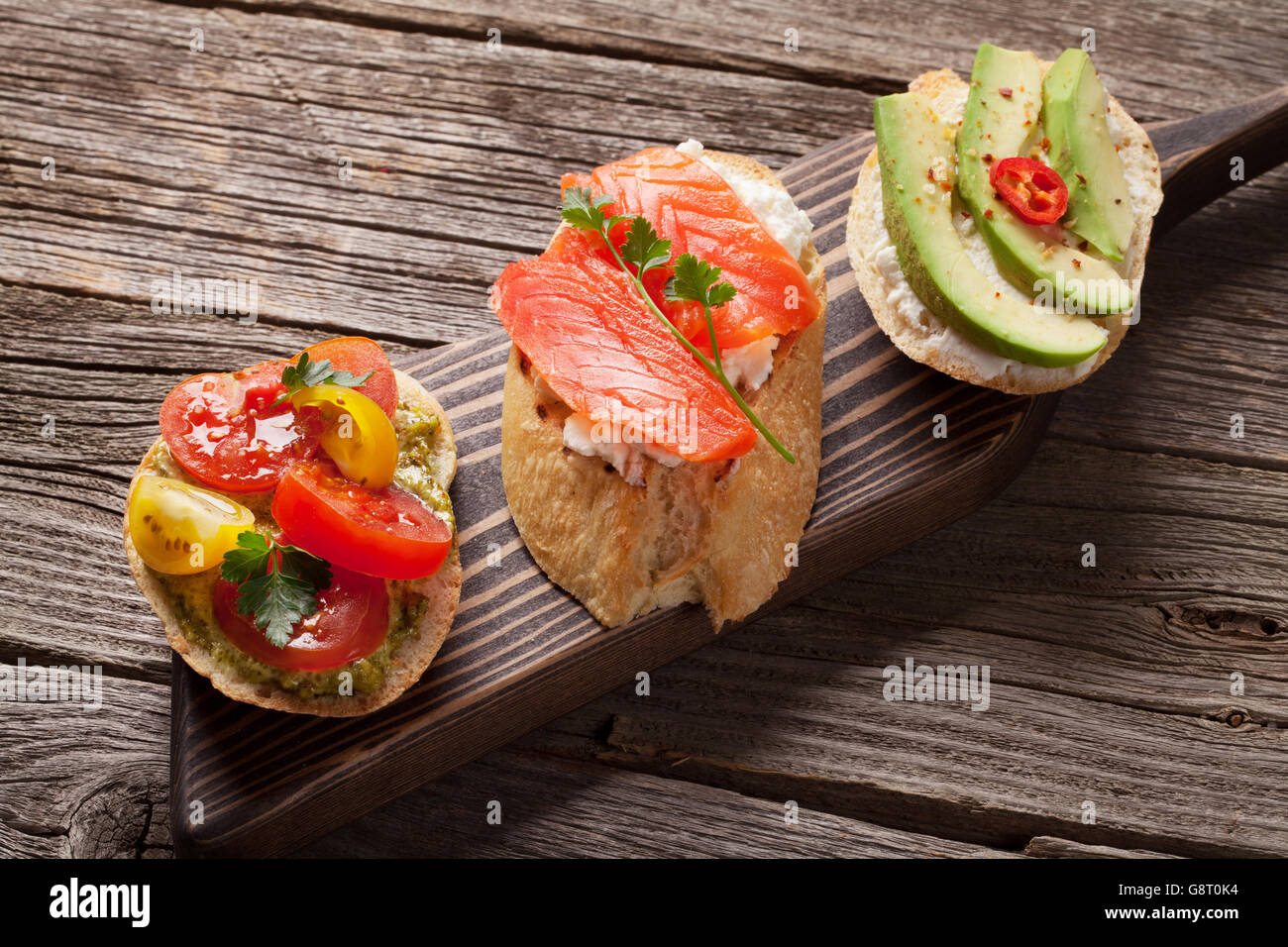 Toast sandwiches with avocado, tomatoes and salmon on wooden background - Stock Image