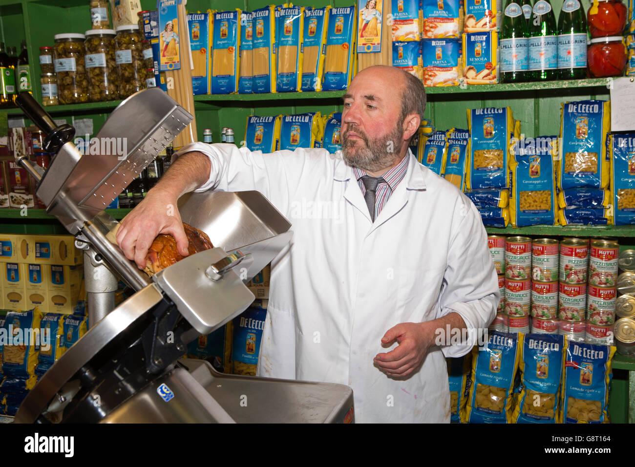 Ireland, Co Sligo, Sligo, Market Square, Michael Cosgrove slicing ham in M Cosgrove and son grocery shop - Stock Image