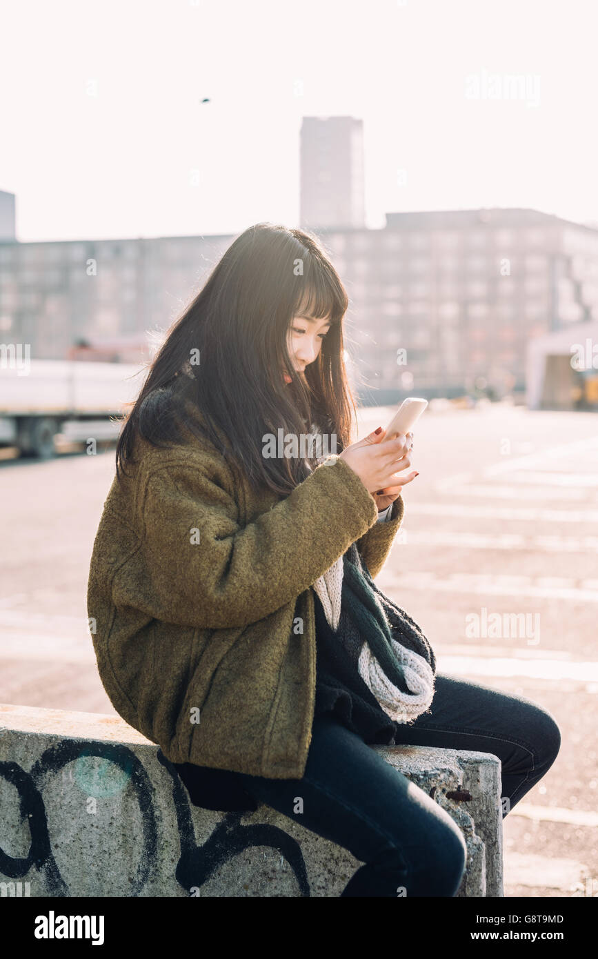 young beautiful asian hipster woman in the city back light using smart phone hand hold, tapping and scrolling the - Stock Image