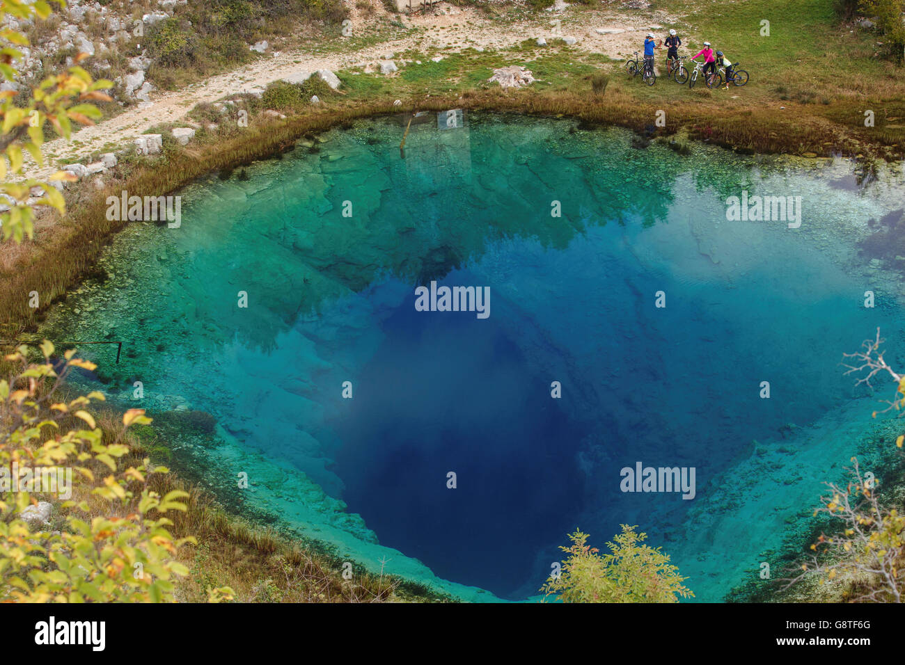 Group of mountain bikers resting on water's edge - Stock Image
