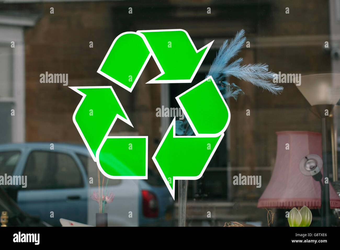 Recycling sign in the window of a shop selling secondhand goods. - Stock Image