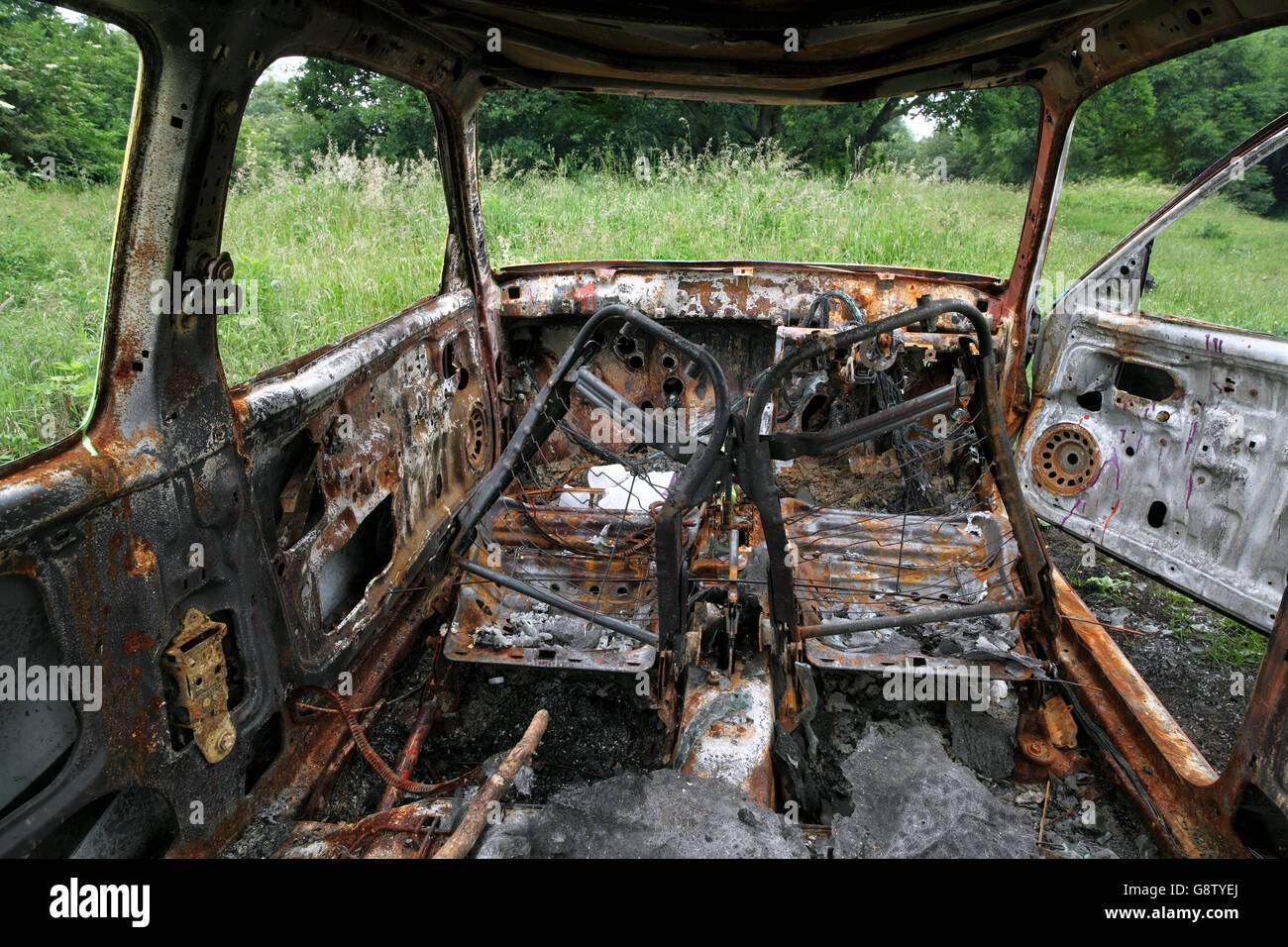 Abandoned and burned out car on the Downs near Brighton. - Stock Image