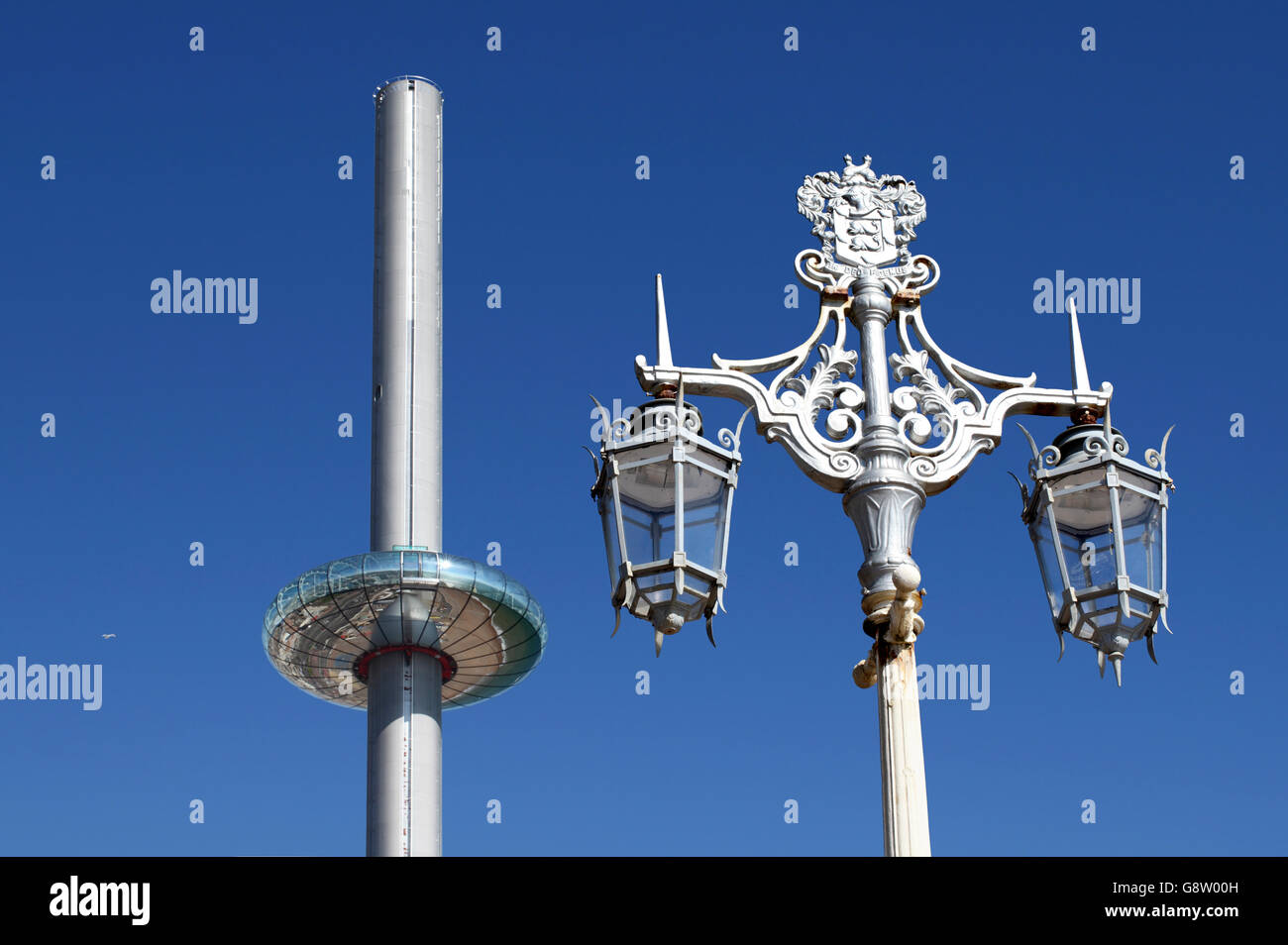Contrasting styles of design on Brighton seafront: the new i360 vertical cable car and a traditional lamppost. - Stock Image