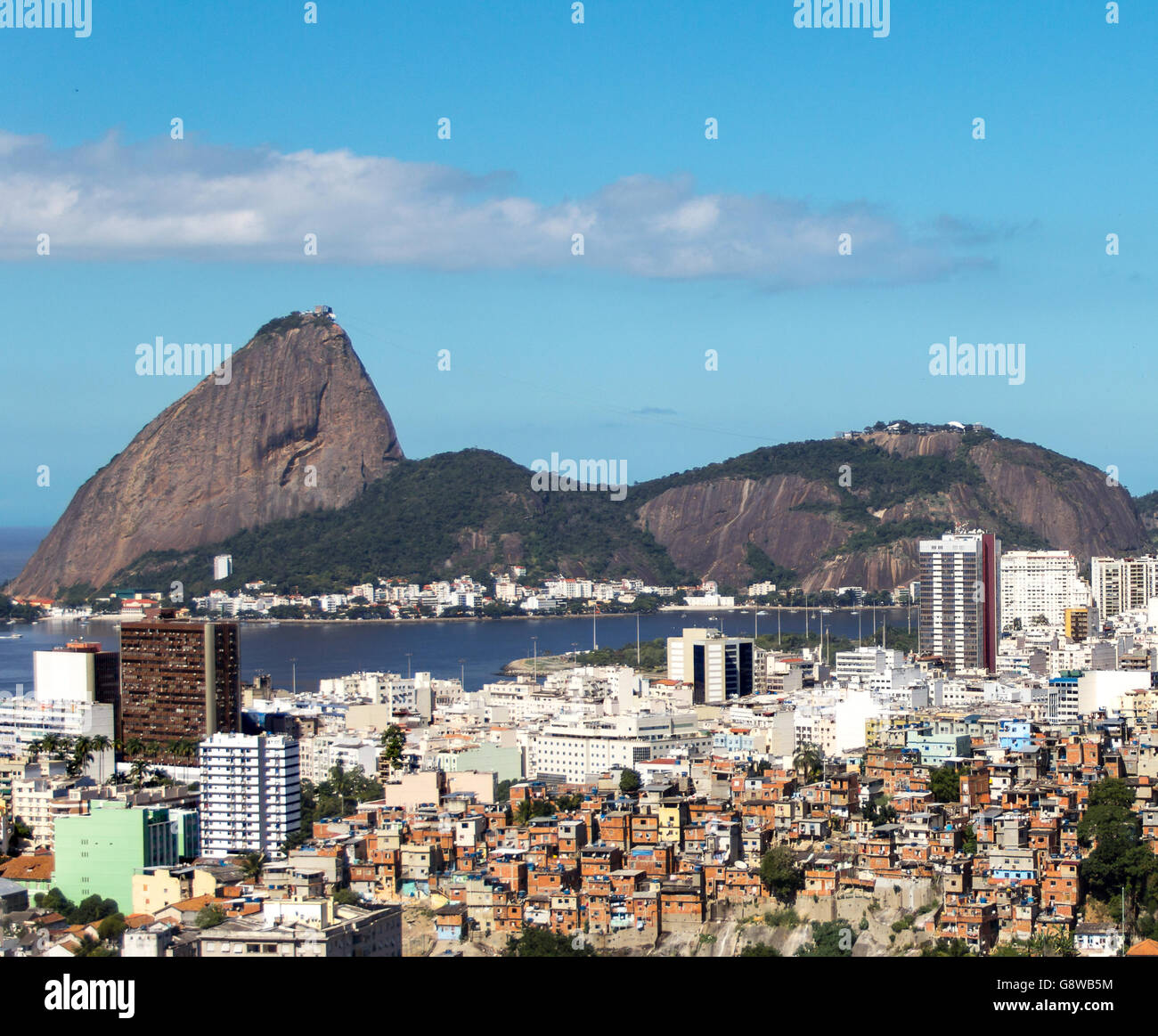 Landmark of Rio de Janeiro: Sugar Loaf. Also social inequality with poor communities and rich neighborhood - Stock Image