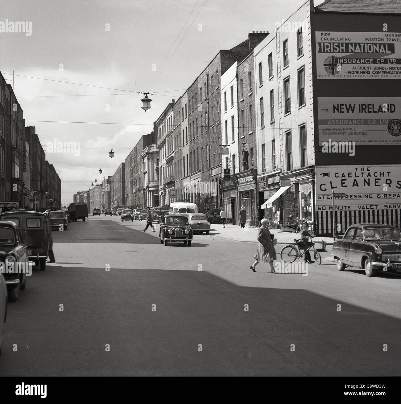 1950s, historical, Ireland, street scene, looking up Lower Cecil St, LImerick, showing cars and billboards of the - Stock Image