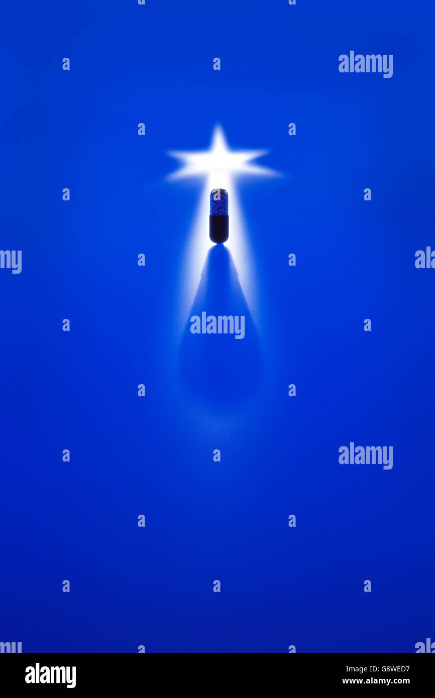 Dramatic shot of pharmaceutical capsule against blue background in semi silhouette - Stock Image