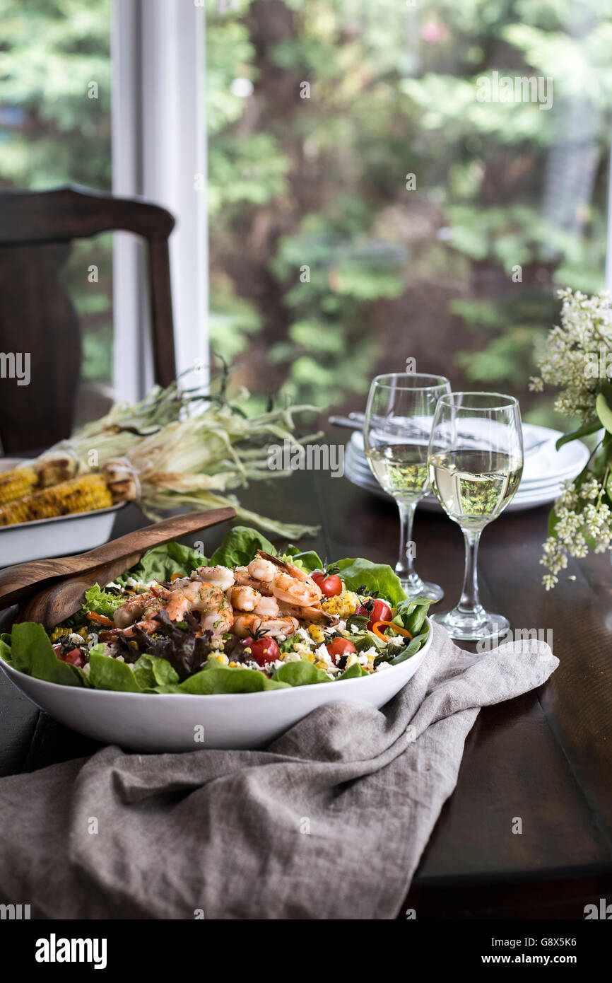 A big bowl of grilled shrimp and corn salad accompanied with two glasses of white wine are photographed from the - Stock Image