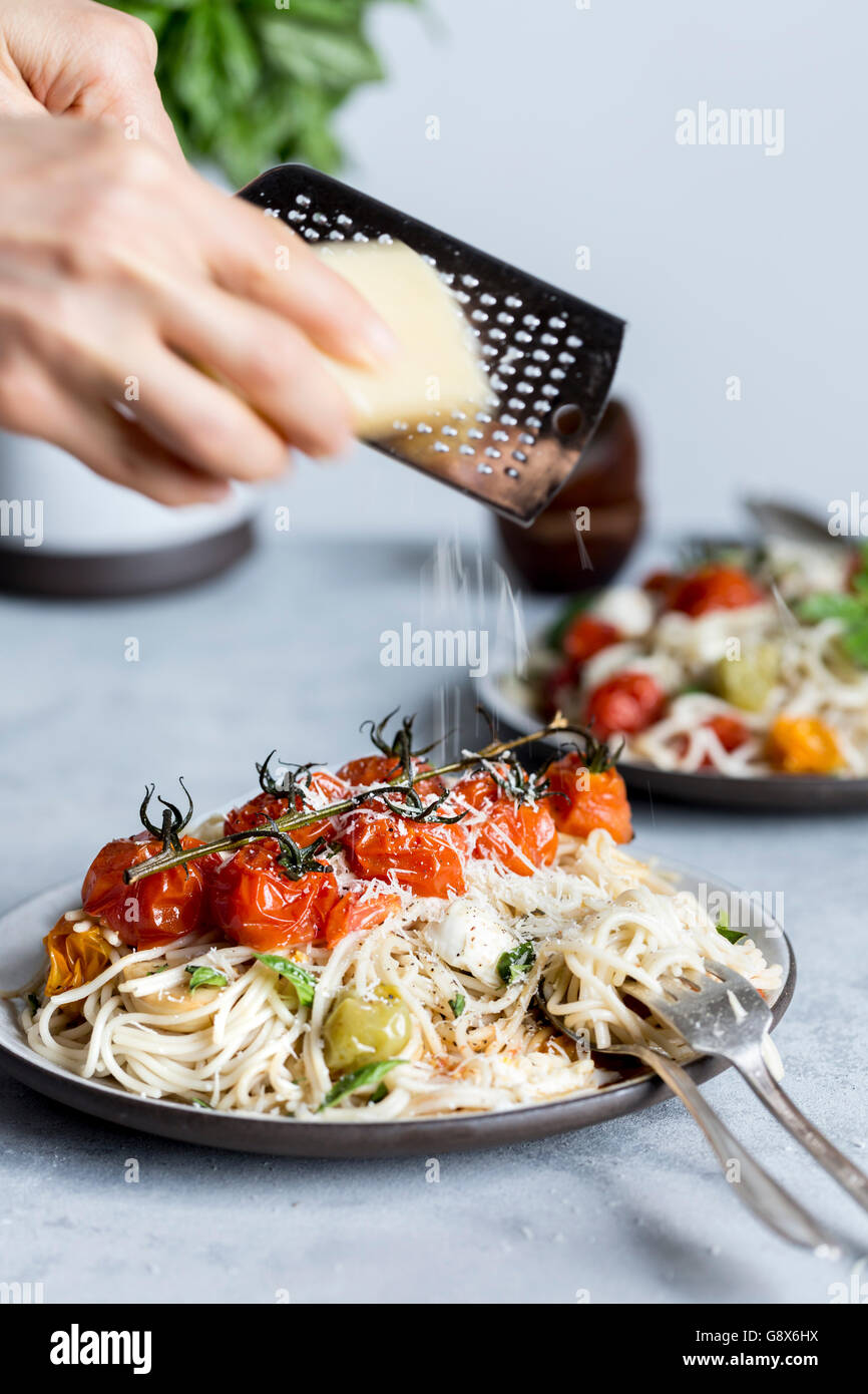A woman is shredding parmesan cheese onto a bowl of spaghetti topped off with roasted tomatoes, mozarella cheese, - Stock Image
