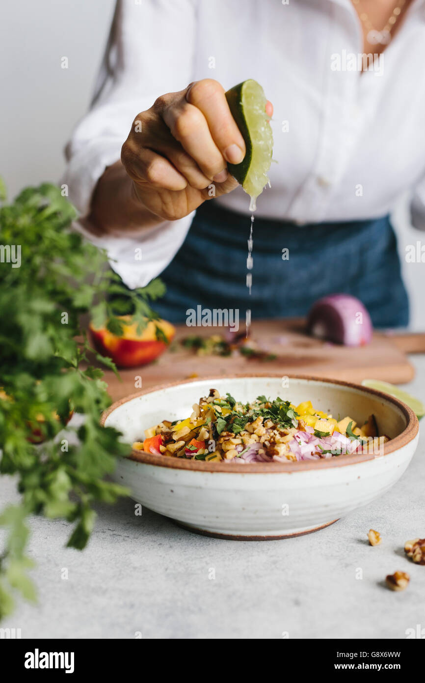 A woman is photographed while she was squeezing lime into a bowl of peach and walnut salsa photographed from the - Stock Image